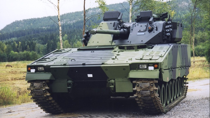 A combat-proven CV9030FIN on a gravel road in front of a green forest. Finland is the latest in a series of CV90 customers to re-invest in the infantry fighting vehicle platform.